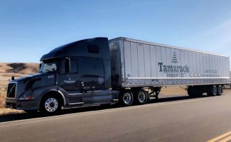 Side View of Tamarack Freight Semi Truck driving down the highway